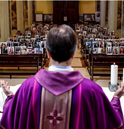 Priest in Rome Standing Before Photos of Quarantined Congregation